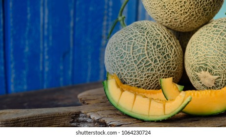 Fresh melons and sliced on wooden table.