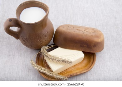fresh milk, butter in a natural pottery on a linen tableclothr