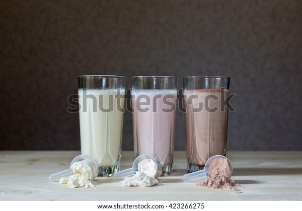 テーブルの上に、新鮮なミルク、チョコレート、ブルーベリー、バナナドリンク、さまざまなタンパク質カクテル。