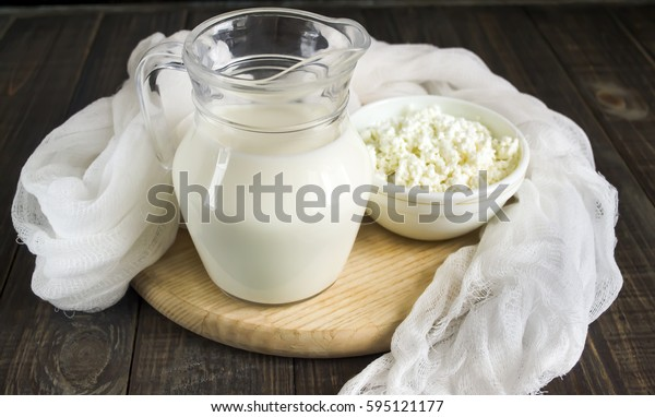 Fresh milk and cottage cheese on a dark wooden background