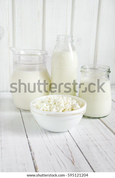 Fresh milk and cottage cheese on a light wooden background