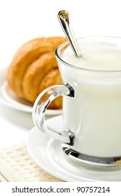 fresh milk in the jug and cup and croissant