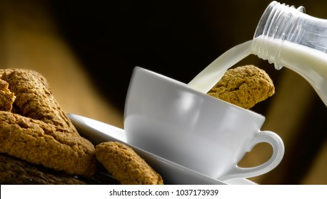 fresh milk poured in a cup with biscuits