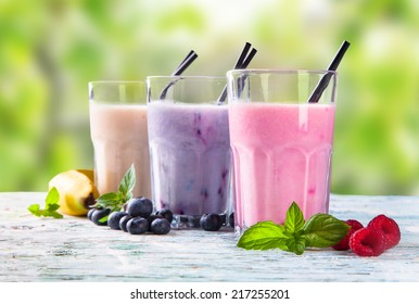 Fresh milk, raspberry, blueberry and banana drinks on wooden table, assorted protein cocktails with fresh fruits.