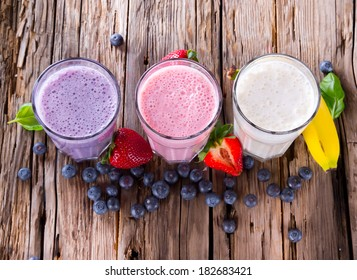 Fresh milk, strawberry, blueberry and banana drinks on wodeen table, assorted protein cocktails with fresh fruits.