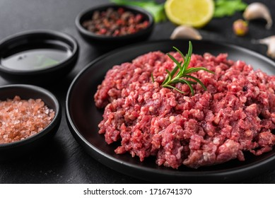Fresh minced meat ground beef on a black plate against stone background - Shutterstock ID 1716741370