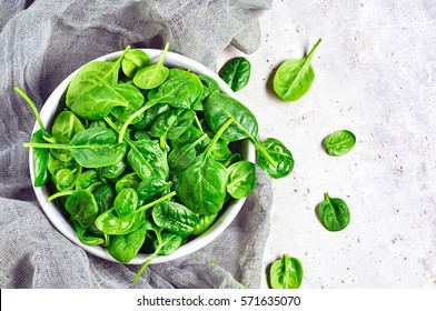 fresh mini spinach in a colander on the old concrete table