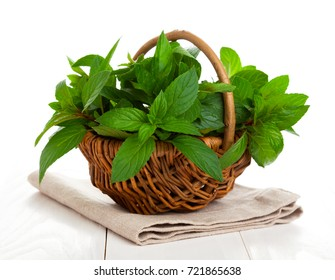 fresh mint in a basket, isolated on a white background