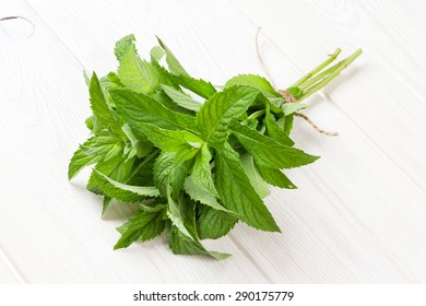 Fresh mint bunch on white wooden table