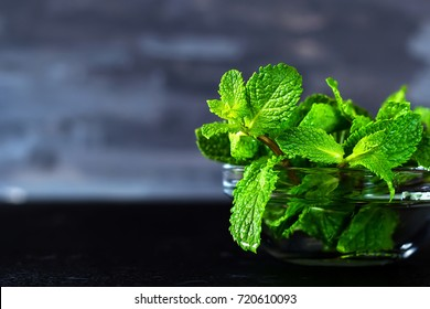 fresh mint into transparent glass cup on black background