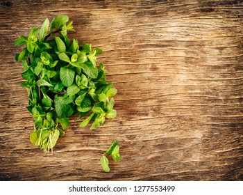 Fresh mint leafs on wooden background, copy space