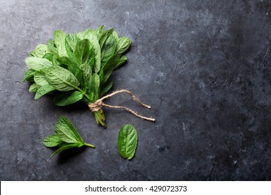 Fresh mint leaves herb on stone table. Top view with copy space