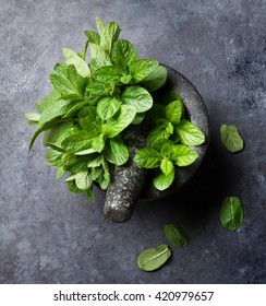 Fresh mint leaves in mortar on stone table. Top view