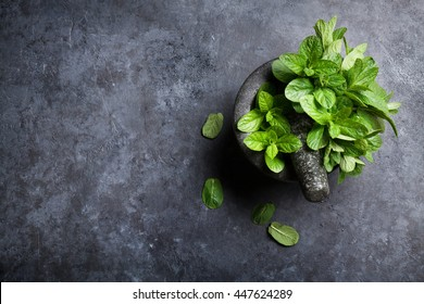 Fresh mint leaves in mortar on stone table. Top view with copy space