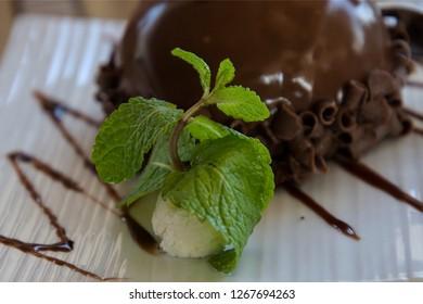 Fresh Mint Leaves next to a Chokolate Ball Cake in a White Plate