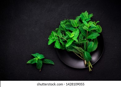 Fresh mint on a black plate on a dark background with a place for your text. top view