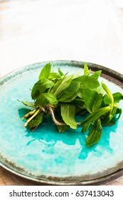 Fresh mint on bright turquoise plate