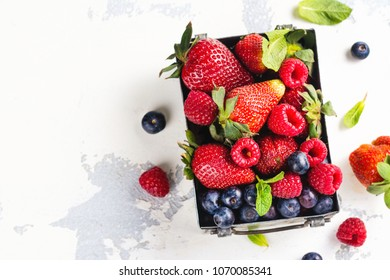 Fresh mix of berries in a metal box on white stone background. Copy space. Toned image