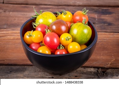 fresh mix of tomatoes variety bowl on rustic table wood plank