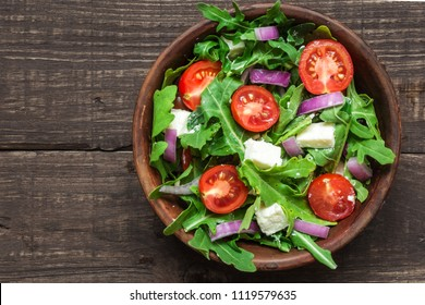 Fresh mixd salad with rucola, tomatoes cherry, feta cheese and red onion in a bowl on rustic wooden table. top view with copy space