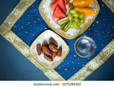 Fresh mixed fruit and sweet dates along with glass of drinking water shot from above. A healthy and nutritious food for breaking fast during holy month of Ramadan.