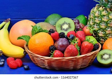 Fresh mixed fruits in a basket on blue wood table