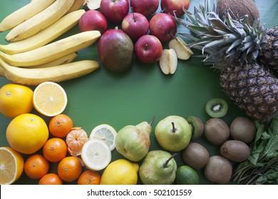 Fresh mixed fruits. Kiwi, mango, bananas, tangerine, lemon, apple, pineapple, orange, mint, ginger, pear, coconut on the green background.