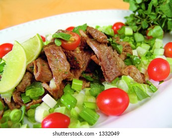 Fresh mixed salad with beef strips and watercress with focus on meat