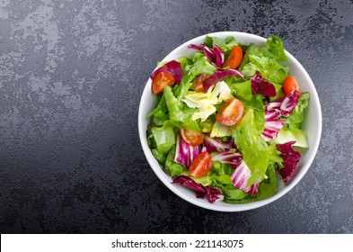Fresh mixed salad with endive and cherry tomatoes on black plate dining, pouring olive oil