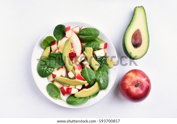 Fresh mixed salad with red apples, avocado, spinach on light background, top view