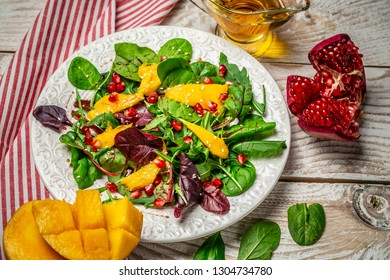Fresh mixed salat with of fresh lettuce, mango, pomegranate and sesame on plate. Diet menu. Food background Top view.