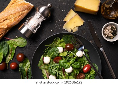 Fresh mixed salat with mozzarella and tomatoes. Healthy food. Top view on table with bread,olive oil,cheese,sunflower seeds,salt and leaves of salat. - Shutterstock ID 1926386192