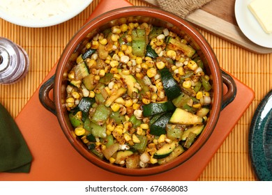 Fresh mixed vegetables cooked with olive oil in a small crockery baking pot.
