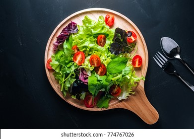 Fresh mixed vegetables salad on a wooden plate