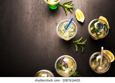 fresh mojito cocktail with lime, mint and blue drinking straw in plastic cup on black background