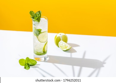 Fresh Mojito cocktail with lime and mint in highball glass with water drops on white and yellow background in bright sun light, Mojito refreshing drinks. Copy space, summer vacation and party concept