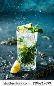 Fresh Mojito cocktail with lime, rosemary, mint and ice in jar glass on dark blue background. Studio shot of drink in freeze motion, drops in liquid splash. Summer cold drink and cocktail