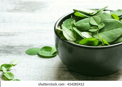 Fresh Moringa leaves in a black bowl, selective focus