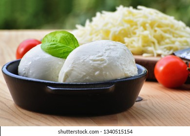 Fresh mozzarella cheese balls in black bowl with cherry tomatoes on the table