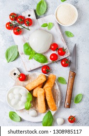 Fresh Mozzarella cheese on vintage chopping board with tomatoes and basil leaf and tray with cheese sticks on stone kitchen background.
