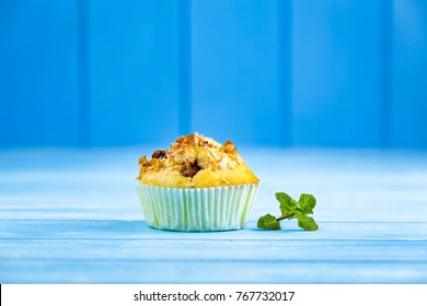 Fresh muffins with nuts and chocolate on the paper cupcake holder. Blue wooden rustic background.