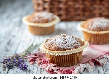 Fresh muffins on a white wooden table