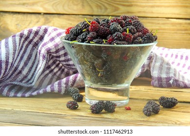 Fresh mulberries in glass cup on wooden board