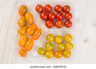 Fresh multicolored cherry tomatoes on wooden background