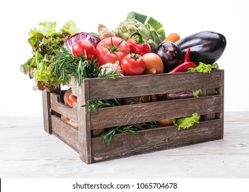 Fresh multi-colored vegetables in wooden crate. Organic food. White background.
