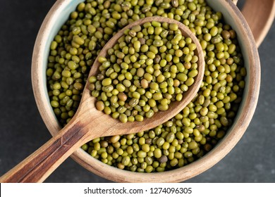 fresh mung beans in ceramic dishes against a dark stone background