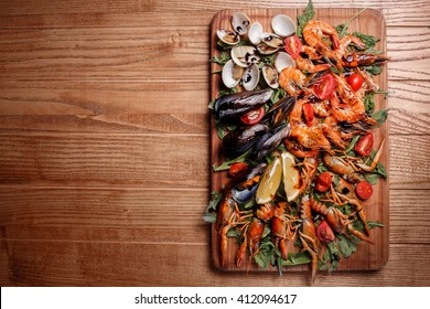 Fresh mussels, crayfish, shrimp decorated with arugula, tomatoes, lemon and sauce on a wooden board. Seafood platter