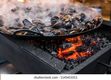 Fresh mussels at grill pan. Seafood barbecue outdoors. Picnic healthy food, mussels in shells. Plenty of mussel shells cooking at large metallic pan.