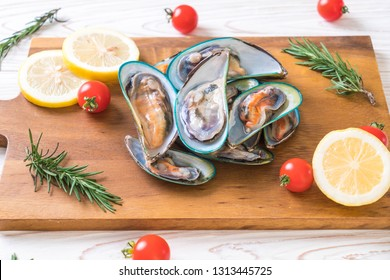 fresh mussels on wooden board with ingredients