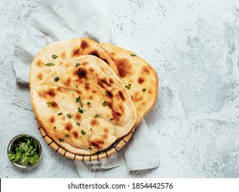 Fresh naan bread on gray cement background with copy space. Top view of several perfect naan flatbreads